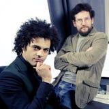 Δύο σοβαροί αρχιτέκτονες που εργάζονται με τον υπολογιστή στο γραφείο που φαίνεται κάμερα Στοκ Φωτογραφία