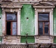Δύο σπασμένα ξύλινα παράθυρα στην πράσινη πρόσοψη τούβλου ενός παλαιού ακτένιστου σπιτιού Στοκ Φωτογραφίες