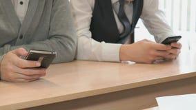 Δύο σπουδαστές που κρατούν smartphones φιλμ μικρού μήκους