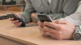 Δύο σπουδαστές που κρατούν smartphones απόθεμα βίντεο