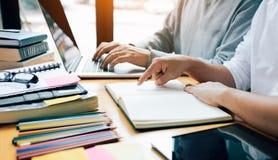 Δύο σπουδαστές που μελετούν και που μαθαίνουν στη βιβλιοθήκη με ένα lap-top και στοκ εικόνες με δικαίωμα ελεύθερης χρήσης