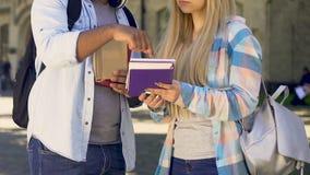 Δύο σπουδαστές που στέκονται μαζί, τύπος που εξηγούν τον τρόπο στο κορίτσι, πρεσβύτερος και καινούριος απόθεμα βίντεο