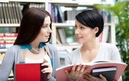 Δύο σπουδαστές που διαβάζονται στη βιβλιοθήκη Στοκ Φωτογραφίες