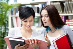 Δύο σπουδαστές που διαβάζονται τα βιβλία στη βιβλιοθήκη Στοκ φωτογραφίες με δικαίωμα ελεύθερης χρήσης
