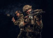 Δύο στρατιώτες ειδικών δυνάμεων στα πλήρη επιθετικά τουφέκια εκμετάλλευσης προστατευτικού εξοπλισμού και να στοχεύσει στους στόχο στοκ εικόνα με δικαίωμα ελεύθερης χρήσης