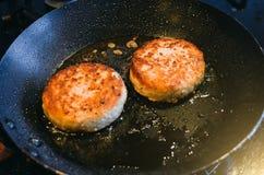 Δύο στρογγυλά cutlets από το κρέας του βόειου κρέατος είναι τηγανισμένα σε ένα τηγανίζοντας τηγάνι και ένα πετρέλαιο Στοκ εικόνα με δικαίωμα ελεύθερης χρήσης