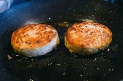 Δύο στρογγυλά cutlets από το κρέας του βόειου κρέατος είναι τηγανισμένα σε ένα τηγανίζοντας τηγάνι και ένα πετρέλαιο Στοκ Εικόνες