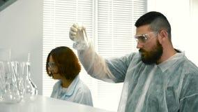 Δύο συγκεντρωμένοι φαρμακοποιοί που εργάζονται στο εργαστήριο απόθεμα βίντεο