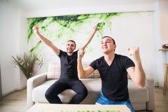 Δύο συγκινημένα άτομα που κάθονται στον καναπέ και ποδόσφαιρο ομάδων προσοχής το αγαπημένο με το στόχο Στοκ φωτογραφία με δικαίωμα ελεύθερης χρήσης