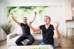 Δύο συγκινημένα άτομα που κάθονται στον καναπέ και ποδόσφαιρο ομάδων προσοχής το αγαπημένο με το στόχο Στοκ εικόνες με δικαίωμα ελεύθερης χρήσης