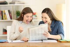 Δύο συγκινημένοι σπουδαστές που διαβάζουν μια εφημερίδα στοκ εικόνες