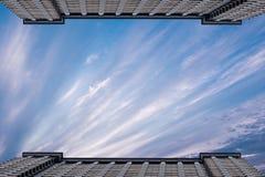 Δύο συμμετρικά ψηλά κτίρια το ένα απέναντι από το άλλο στα πλαίσια ενός νεφελώδους ουρανού Διάστημα για το κείμενο Στοκ εικόνα με δικαίωμα ελεύθερης χρήσης