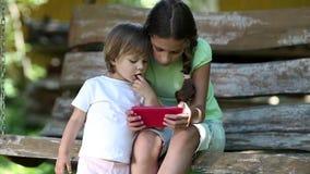 Δύο συμπαθητικά κορίτσια με το κόκκινο smartphone κάθονται στον πάγκο ταλάντευσης στον κήπο φιλμ μικρού μήκους