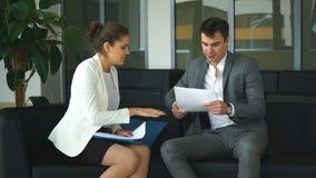 Δύο συνάδελφοι που συζητούν τις επιχειρησιακές ιδέες που κάθονται στις καρέκλες στο γραφείο απόθεμα βίντεο