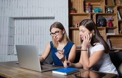 Δύο συνάδελφοι που χρησιμοποιούν το τηλέφωνο καθαρός-βιβλίων και κυττάρων για την ομαδική εργασία στην αρχή στοκ εικόνα