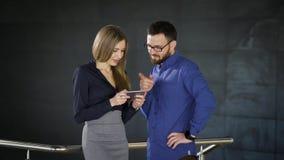 Δύο συνάδελφοι κουβεντιάζουν στο γραφείο και μοιράζονται τις εντυπώσεις για την εργασία τους Το άτομο που ντύνεται στο μπλε πουκά απόθεμα βίντεο