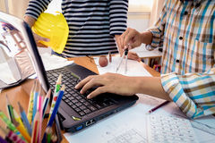 Δύο συνάδελφοι που συζητούν τα στοιχεία που λειτουργούν με το σχέδιο κατασκευής Στοκ εικόνες με δικαίωμα ελεύθερης χρήσης