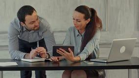 Δύο συνάδελφοι συζητούν γύρω από μια ψηφιακή ταμπλέτα απόθεμα βίντεο