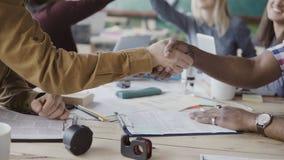Δύο συνεργάτες, αφρικανικά και καυκάσια χέρια κουνημάτων επιχειρηματιών Ομάδα ανθρώπων που χτυπά επάνω ένα υπόβαθρο στο σύγχρονο  φιλμ μικρού μήκους
