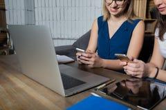 Δύο συνεργάτες που κουβεντιάζουν στα κινητά τηλέφωνα στο κοινωνικό δίκτυο περιμένοντας την τηλεοπτική κλήση στο φορητό προσωπικό  στοκ φωτογραφία με δικαίωμα ελεύθερης χρήσης