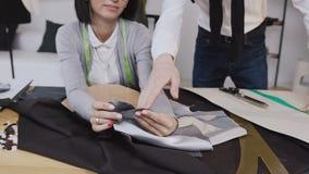 Δύο σχεδιαστές μόδας ανθρώπων που επιλέγουν το ύφασμα στο γραφείο με τα διαφορετικά εργαλεία και τα ενδύματα προσαρμογής Νέα γυνα φιλμ μικρού μήκους