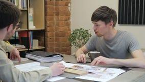 Δύο σχεδιαστές που αναπτύσσουν την εσωτερική συνεδρίαση σχεδίου στην αρχή της επιχείρησης απόθεμα βίντεο