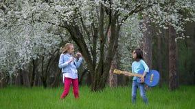 Δύο σχολικές φίλες οργάνωσαν απόδοσης βράχου δασικά την άνοιξη γύρω από το άλμα και το γέλιο με μια κιθάρα διαθέσιμη Flowe φιλμ μικρού μήκους
