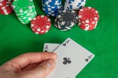 Δύο σωρός άσσων και τσιπ πόκερ στον πράσινο πίνακα Στοκ Εικόνες