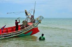 Δύο ταϊλανδικοί ψαράδες προετοιμάζουν τη βάρκα με την άγκυρα στην παραλία Pattani Ταϊλάνδη στοκ φωτογραφίες