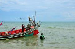 Δύο ταϊλανδικοί ψαράδες προετοιμάζουν τη βάρκα με την άγκυρα στην παραλία Pattani Ταϊλάνδη στοκ εικόνες