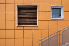 Δύο τεχνικά παράθυρα στον πορτοκαλή κεραμωμένο τοίχο με την αερισμένη πρόσοψη στοκ φωτογραφία με δικαίωμα ελεύθερης χρήσης