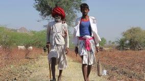 Δύο τοπικοί ινδικοί φύλακες βοοειδών που περπατούν κάτω από το δρόμο από έναν τομέα στο Jodhpur φιλμ μικρού μήκους