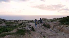Δύο τουρίστες πηγαίνουν στην άκρη του απότομου βράχου να εξετάσουν στη θάλασσα, στο ηλιοβασίλεμα, και την καταπληκτική φύση Δύσκο απόθεμα βίντεο