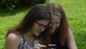 Δύο το κορίτσια που γελούν κατά χρησιμοποίηση του κινητού τηλεφώνου απόθεμα βίντεο