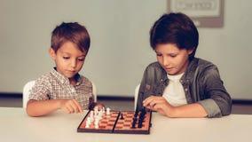 Δύο τρυπημένα αγόρια που παίζουν τη συνεδρίαση σκακιού στον πίνακα στοκ φωτογραφίες με δικαίωμα ελεύθερης χρήσης