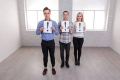 Δύο τύποι και ένα κορίτσι στέκονται και τα φύλλα εγγράφου λαβής με ένα θαυμαστικό Στοκ εικόνα με δικαίωμα ελεύθερης χρήσης