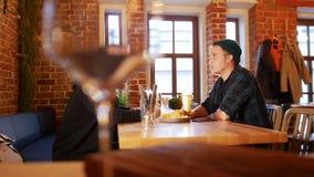 Δύο τύποι που κάθονται σε έναν πίνακα σε ένα εστιατόριο Ζευγάρι των γυαλιών στο πρώτο πλάνο φιλμ μικρού μήκους