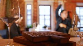 Δύο τύποι που κάθονται σε έναν πίνακα σε ένα εστιατόριο και που καλούν το σερβιτόρο Ζευγάρι των γυαλιών στην εστίαση απόθεμα βίντεο