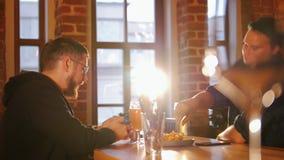 Δύο τύποι που κάθονται σε έναν πίνακα σε ένα εστιατόριο και μια μπύρα κατανάλωσης Ένας από τους που καλούν κάποιο απόθεμα βίντεο