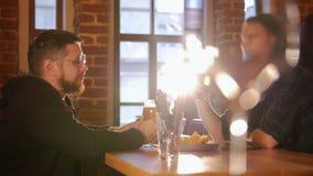 Δύο τύποι που κάθονται σε έναν πίνακα σε ένα εστιατόριο και μια μπύρα κατανάλωσης απόθεμα βίντεο
