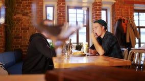 Δύο τύποι που κάθονται σε έναν πίνακα σε ένα εστιατόριο και που μιλούν ο ένας στον άλλο φιλμ μικρού μήκους