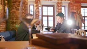 Δύο τύποι που κάθονται σε έναν πίνακα σε ένα εστιατόριο και που μιλούν στο τηλέφωνο απόθεμα βίντεο