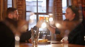 Δύο τύποι που κάθονται σε έναν πίνακα σε ένα εστιατόριο, κατανάλωση Ζευγάρι των γυαλιών στο πρώτο πλάνο φιλμ μικρού μήκους