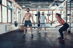 Δύο τύποι στη γυμναστική που ανυψώνουν Barbell Ενισχυτικό κορίτσι στοκ φωτογραφίες με δικαίωμα ελεύθερης χρήσης