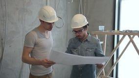 Δύο υπάλληλοι ατόμων που εξετάζουν το σχέδιο επισκευής που στέκεται στο εσωτερικό φιλμ μικρού μήκους
