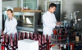 Δύο υπάλληλοι στα παλτά που στέκονται στη συσκευασία του τμήματος ατόμου κρασιού Στοκ φωτογραφία με δικαίωμα ελεύθερης χρήσης