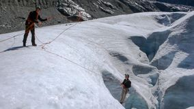 Δύο υποψήφιοι οδηγών βουνών που ασκούν crevasse τη διάσωση σε έναν παγετώνα στις Άλπεις στοκ φωτογραφίες