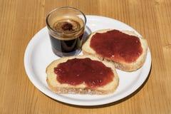 Δύο φέτες του ψωμιού με τη μαρμελάδα και το ποτό φραουλών Στοκ Φωτογραφίες