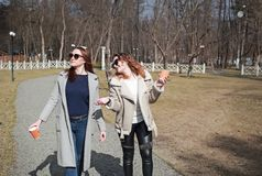 Δύο φίλες γυναικών πίνουν τον καφέ στο πάρκο στοκ εικόνα με δικαίωμα ελεύθερης χρήσης