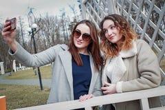 Δύο φίλες γυναικών πίνουν τον καφέ στο πάρκο στοκ εικόνες με δικαίωμα ελεύθερης χρήσης